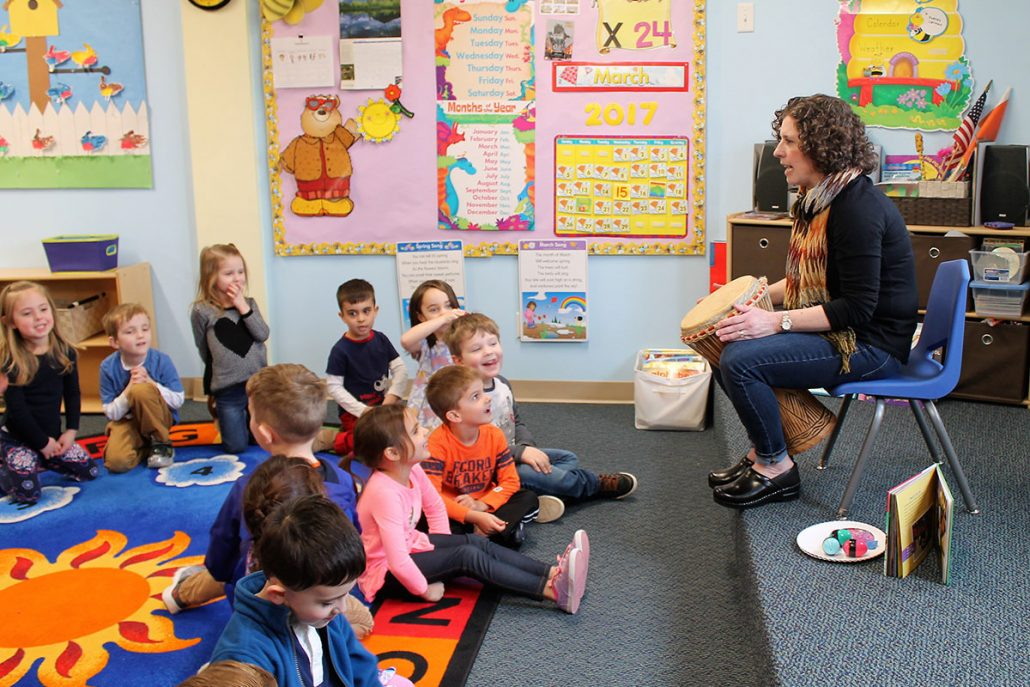 Teacher with music instrument teaching children with music